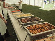 Uncovered outdoor buffet line at a catered hog roast event