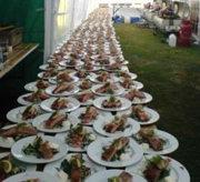 An enormous table lined with hot smoked salmon starters ready to serve